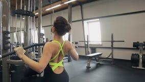Η αθλητική γυναίκα χρησιμοποιεί μια pull-down lat συνεδρίαση μηχανών πίσω στη κάμερα φιλμ μικρού μήκους