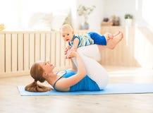 Η αθλητική μητέρα συμμετέχει στην ικανότητα και τη γιόγκα με το μωρό στο σπίτι στοκ φωτογραφία