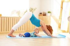 Η αθλητική μητέρα συμμετέχει στην ικανότητα και τη γιόγκα με το μωρό στο σπίτι στοκ φωτογραφία με δικαίωμα ελεύθερης χρήσης