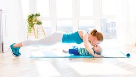 Η αθλητική μητέρα συμμετέχει στην ικανότητα και τη γιόγκα με το μωρό στο σπίτι Στοκ Εικόνες