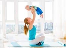 Η αθλητική μητέρα συμμετέχει στην ικανότητα και τη γιόγκα με το μωρό στο σπίτι στοκ εικόνα