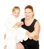 Η αθλητική οικογένεια mom διδάσκει την κόρη για να κτυπήσει το λάκτισμα που μονώνεται Στοκ εικόνα με δικαίωμα ελεύθερης χρήσης
