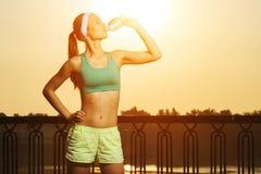 Η αθλητική όμορφη αθλήτρια πίνει το καθαρό νερό από στοκ εικόνες