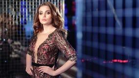 Η αισθησιακή όμορφη νέα γυναίκα που φορούν το εκλεκτής ποιότητας φόρεμα πολυτέλειας και η γοητεία ετοιμάζουν στο υπόβαθρο disco απόθεμα βίντεο