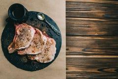Η ακατέργαστα μπριζόλα και τα καρυκεύματα χοιρινού κρέατος φρέσκου κρέατος σε μια σκοτεινή ξύλινη ντομάτα μελιού πινάκων υποβάθρο στοκ εικόνες με δικαίωμα ελεύθερης χρήσης