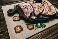Η ακατέργαστα μπριζόλα και τα καρυκεύματα χοιρινού κρέατος φρέσκου κρέατος σε μια σκοτεινή ξύλινη ντομάτα μελιού πινάκων υποβάθρο στοκ φωτογραφία με δικαίωμα ελεύθερης χρήσης