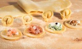 Η ακατέργαστη ζύμη και το ιταλικό σπιτικό tortellini, ανοικτός και κλειστός, γέμισαν με το τυρί ricotta, τις γαρίδες, το prosciut Στοκ Εικόνα