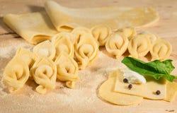 Η ακατέργαστη ζύμη και το ιταλικό σπιτικό tortellini, ανοικτός και κλειστός, γέμισαν με το τυρί ricotta και το φρέσκο σπανάκι Στοκ εικόνα με δικαίωμα ελεύθερης χρήσης