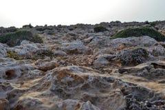 Η ακτή καλύπτεται με τις αιχμηρές πέτρες Μια άψυχη παραλία πετρών σύσταση Στοκ Εικόνα