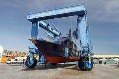 Η ακτοφυλακή του ισπανικού τελωνείου πέρα από ένα travelift πριν από πηγαίνει στο νερό στοκ εικόνες