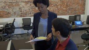Η δακτυλογράφηση επιχειρησιακών γυναικών αφροαμερικάνων που χρησιμοποιεί το φορητό προσωπικό υπολογιστή επικοινωνεί με τον ασιατι απόθεμα βίντεο