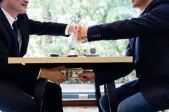 Η αλλοιωμένη σφράγιση δύο επιχειρηματιών εξετάζει μια χειραψία και λήψη χρημάτων δωροδοκιών στοκ φωτογραφία