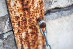 Η αλυσίδα είναι συνδεμένη με τον τοίχο με ένα σκουριασμένο μπουλόνι στοκ φωτογραφία