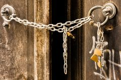 Η αλυσίδα μετάλλων κλείνει μια παλαιά πόρτα ενός εγκαταλειμμένου σπιτιού στοκ εικόνες
