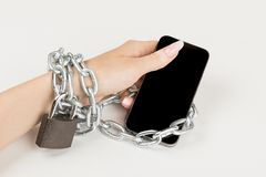 η αλυσίδα σιδήρου με την κλειδαριά συνδέει το θηλυκό χέρι και το smartphone η έννοια της εξάρτησης στο κινητό τηλέφωνο στοκ φωτογραφία με δικαίωμα ελεύθερης χρήσης