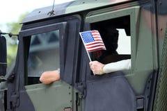 Η ΑΜΕΡΙΚΑΝΙΚΗ σημαία παραμερίζει από ένα στρατιωτικό όχημα Στοκ Φωτογραφία