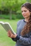 η ανάγνωση κοριτσιών βιβλίων χαλάρωσε τις νεολαίες Στοκ Φωτογραφίες