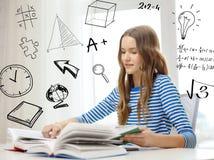 Η ανάγνωση κοριτσιών σπουδαστών χαμόγελου κρατά στο σπίτι Στοκ φωτογραφία με δικαίωμα ελεύθερης χρήσης