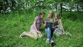 Η ανάγνωση μητέρων κρατά τις κόρες τους στο πάρκο απόθεμα βίντεο