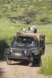 Η ανίχνευση και οι τουρίστες Masai ψάχνουν τα ζώα από ένα Landcruiser κατά τη διάρκεια μιας κίνησης παιχνιδιών στη συντήρηση άγρι Στοκ Εικόνες