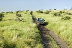 Η ανίχνευση και οι τουρίστες Masai ψάχνουν τα ζώα από ένα Landcruiser κατά τη διάρκεια μιας κίνησης παιχνιδιών στη συντήρηση άγρι Στοκ Εικόνα