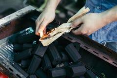 Η αναμμένη πυρκαγιά σε χαρτί για το κάψιμο του ξυλάνθρακα στη σόμπα, προετοιμάζεται για το ψήσιμο στη σχάρα των τροφίμων στη Μπαν Στοκ Εικόνες