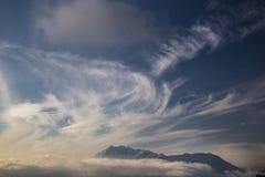 η ανασκόπηση καλύπτει τα νεφελώδη βουνά κάλυψης φυσικά πέρα από τον ουρανό Στοκ Φωτογραφίες