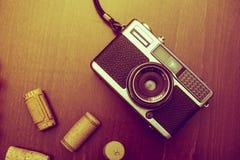 Η αναδρομικά κάμερα και το κρασί βουλώνουν στο ξύλινο επιτραπέζιο υπόβαθρο, τρύγος ομο Στοκ Φωτογραφία