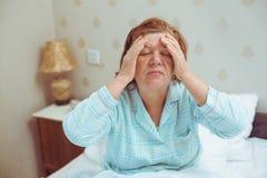 Η ανησυχημένη ηλικιωμένη γυναίκα έχει τον πονοκέφαλο στο σπίτι στοκ φωτογραφίες