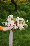 Η ανθοδέσμη της νύφης Η γυναίκα λουλουδιών κρατά στο χέρι της μια όμορφη γαμήλια ανθοδέσμη των λουλουδιών για τη νύφη στοκ φωτογραφία με δικαίωμα ελεύθερης χρήσης