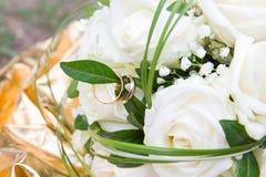Η ανθοδέσμη των άσπρων τριαντάφυλλων με την κινηματογράφηση σε πρώτο πλάνο των χρυσών γαμήλιων δαχτυλιδιών στο λευκό αυξήθηκε Στοκ Φωτογραφίες