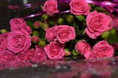 Η ανθοδέσμη των ερυθρών τριαντάφυλλων σε ένα γκρίζο υπόβαθρο, όμορφα λουλούδια με το νερό μειώνεται στοκ φωτογραφία με δικαίωμα ελεύθερης χρήσης