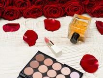 Η ανθοδέσμη των κόκκινων τριαντάφυλλων, της παλέτας αρώματος, κραγιόν και σκιάς ματιών βρίσκεται σε έναν άσπρο ξύλινο πίνακα Στοκ φωτογραφία με δικαίωμα ελεύθερης χρήσης