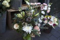 Η ανθοδέσμη των λουλουδιών από τα χρυσάνθεμα, τα κόκκινους μούρα και τους κώνους σε μια αγορά λουλουδιών για την πώληση Στοκ Εικόνες