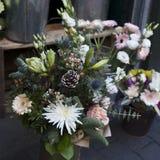 Η ανθοδέσμη των λουλουδιών από τα χρυσάνθεμα, τα κόκκινους μούρα και τους κώνους σε μια αγορά λουλουδιών για την πώληση Στοκ Φωτογραφίες