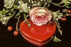 Η ανθοδέσμη από τα άσπρα λουλούδια, αυξήθηκε και ξεραίνει τους κλαδίσκους και την κόκκινη καρδιά κιβωτίων με τις σοκολάτες Στοκ εικόνα με δικαίωμα ελεύθερης χρήσης