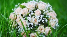 Η ανθοδέσμη μιας νύφης των ρόδινων τριαντάφυλλων βρίσκεται στη χλόη στο πάρκο φιλμ μικρού μήκους