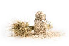 Η ανθοδέσμη σιταριού, χρυσά spikelets βρωμών και μπορεί γεμισμένος με τα ξηρά σιτάρια στον άσπρο πίνακα Τρόφιμα και βάζο Στοκ Εικόνες