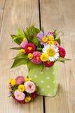 Η ανθοδέσμη των ζωηρόχρωμων άγριων λουλουδιών σε πράσινο που διαστίζονται μπορεί Στοκ Εικόνες