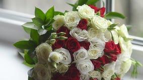 Η ανθοδέσμη των κόκκινων και άσπρων τριαντάφυλλων βρίσκεται στο παράθυρο, όμορφα ζωηρόχρωμα λουλούδια που το διαθέσιμο άτομο χερι απόθεμα βίντεο