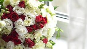 Η ανθοδέσμη των κόκκινων και άσπρων τριαντάφυλλων βρίσκεται στο παράθυρο, τα όμορφα ζωηρόχρωμα λουλούδια είναι στον πίνακα απόθεμα βίντεο