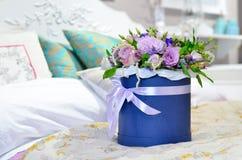 Η ανθοδέσμη των τριαντάφυλλων σε ένα μπλε κιβώτιο είναι στο κρεβάτι Στοκ Εικόνες