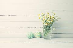 Η ανθοδέσμη των chamomiles σε ένα βάζο γυαλιού και τα αυγά Πάσχας στην κρητιδογραφία χρωματίζουν στον άσπρο ξύλινο πίνακα Στοκ Φωτογραφία