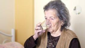 η ανθυγειινή ηλικιωμένη γυναίκα παίρνει τα χάπια, πίνει το νερό απόθεμα βίντεο