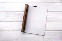 Η ανοιγμένη κενή άσπρη χλεύη επάνω στη σελίδα περιοδικών στην άσπρη ξύλινη ετικέττα στοκ φωτογραφία με δικαίωμα ελεύθερης χρήσης