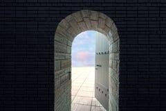 Η ανοιχτή πόρτα του παλαιού κάστρου μέσω του οποίου μπορείτε να δείτε το μπλε ουρανό με τα σύννεφα Ωοειδής αψίδα της πόρτας στοκ φωτογραφία με δικαίωμα ελεύθερης χρήσης