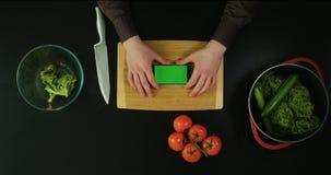 Η ανωτέρω άποψη των χεριών σχετικά με το κινητό τηλέφωνο που τοποθετείται στον ξύλινο πίνακα Η minimalistic φυτική σύνθεση απόθεμα βίντεο