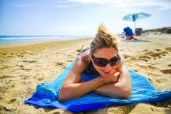 Η ανύπαντρη καθορίζει την κενή θερινή παραλία μαυρίσματος πετσετών παραλιών χαμογελώντας τα μεγάλα γυαλιά ηλίου Στοκ φωτογραφία με δικαίωμα ελεύθερης χρήσης