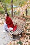 Η ανώνυμη γυναίκα που απολαμβάνει το take-$l*away φλυτζάνι καφέ την ηλιόλουστη κρύα ημέρα πτώσης κάθεται στον πάγκο στοκ εικόνα με δικαίωμα ελεύθερης χρήσης