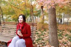 Η ανώνυμη γυναίκα που απολαμβάνει το take-$l*away φλυτζάνι καφέ την ηλιόλουστη κρύα ημέρα πτώσης κάθεται στον πάγκο στοκ φωτογραφία